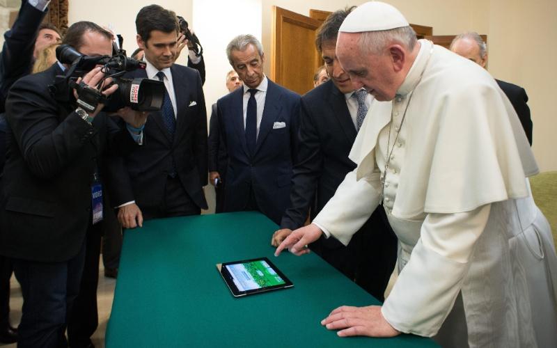 """20.mar.2014 - Papa Francisco usa tablet durante evento no Vaticano, para promover a Scholas Occurrentes, uma rede que tem o objetivo de compartilhar ideais entre escolas de todo o mundo. Com mais de 3,8 milhões de seguidores, ele publicou um tuíte no qual incentivou a iniciativa e divulgou o perfil @infoscholas. """"Hoje plantamos a primeira árvore virtual para a paz"""", escreveu o papa"""