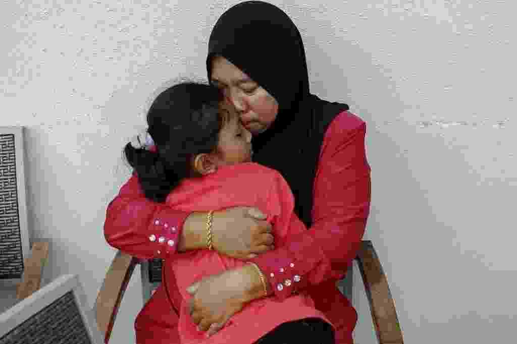 20.mar.2014 - Rosila Abu Samah, 50, e sua filha Kaiyisah Selamat, 8, mãe e irmã do engenheiro de voo Mohd Khairul Amri Selamat que estava a bordo do MH370, desaparecido desde 8 de março, se abraçam durante uma entrevista onde parentes dos passageiros Boeing estão hospedados - Samsul Said/Reuters
