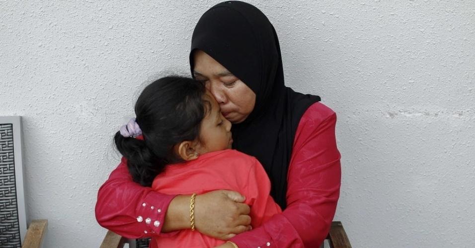 20.mar.2014 - Rosila Abu Samah, 50, e sua filha Kaiyisah Selamat, 8, mãe e irmã do engenheiro de voo Mohd Khairul Amri Selamat que estava a bordo do MH370, desaparecido desde 8 de março, se abraçam durante uma entrevista onde parentes dos passageiros Boeing estão hospedados