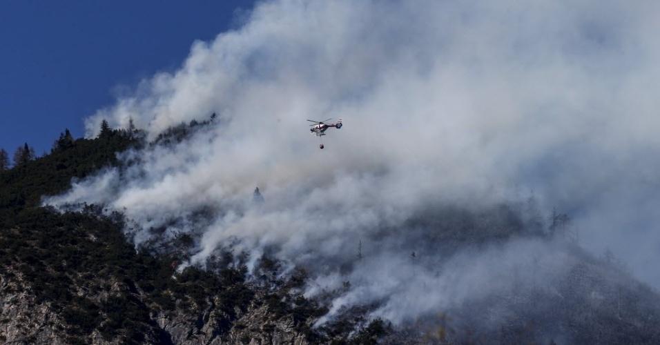 20.mar.2014 - Um helicóptero da polícia joga água sobre um incêndio florestal em Runstboden, uma montanha na aldeia austríaca Absam