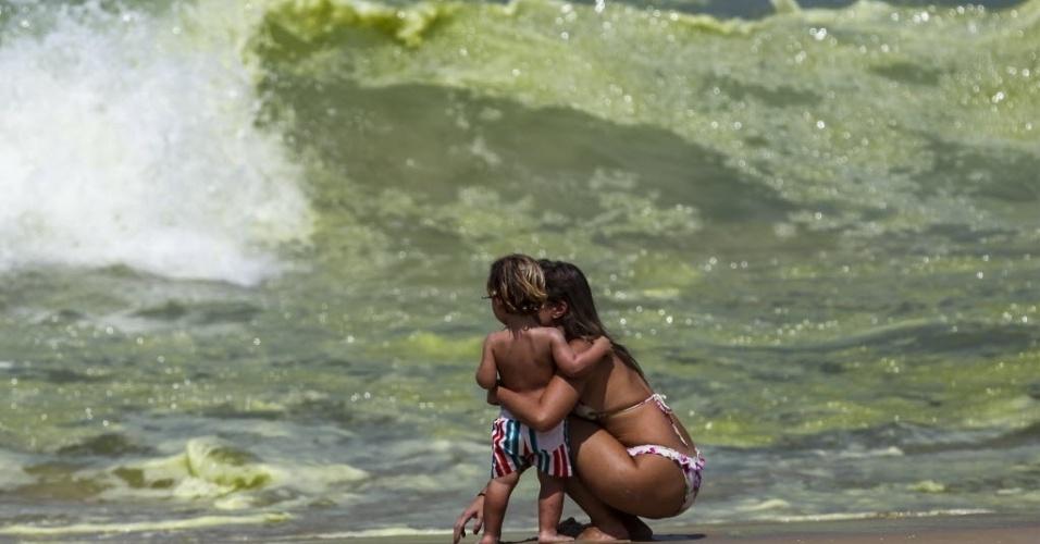 21.mar.2014 - Mulher observa a coloração verde da água da praia de Ipanema, no Rio de Janeiro, nesta sexta-feira (21). A mudança nas águas acontece devido à presença de algas