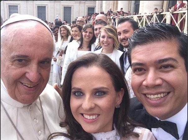 """Dois recém-casados conseguiram tirar um """"selfie"""" (autorretrato) com o papa Francisco durante audiência geral semanal no Vaticano. Não é a primeira vez que o papa posa para fotos com fieis, em agosto do ano passado ele foi retratado ao lado de adolescentes que visitavam o Vaticano"""