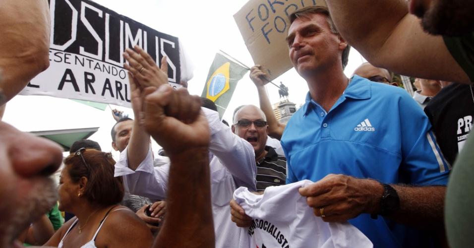 """22.mar.2014 -  O deputado federal Jair Bolsonaro (PP-RJ) participa da Marcha da Família com Deus pela Liberdade na Central do Brasil, neste sábado (22), no Rio de Janeiro. Cantando músicas de ordem, com versos que dizem """"Não abro mão, quero intervenção"""", os manifestantes pedem pela intervenção militar contra a corrupção e a defesa da família. """"Estou aqui como cidadão e acho muito válido esse protesto de pessoas de bem que querem o fim da corrupção, mas acho que o pedido de intervenção militar tira um pouco da força do protesto"""", afirmou o deputado"""