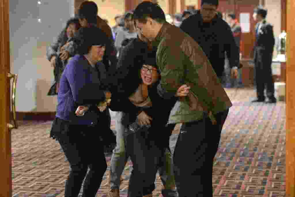 """24.mar.2014 - Familiares dos passageiros do vôo MH370, da Malaysia Airlines, saem em choque de uma sala no hotel Lido, em Pequim, na China, nesta segunda-feira (24), após serem informados de que a aeronave caiu no sul do oceano Índico e que não há sobreviventes entre os 239 ocupantes. A  companhia aérea informou que os parentes podem ser levados para uma """"área de recuperação"""", para se estabilizar após 17 dias de angústia sem ter informações sobre o paradeiro do avião - Goh Chai Hin/AFP"""