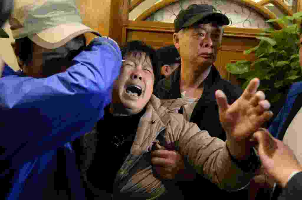 24.mar.2014 - Familiares dos passageiros do voo MH370 da Malaysian Airlines choram após o anuncio do premiê da Malásia, Najib Razak, de que a aeronave caiu no sul do oceano Índico e que não há sobreviventes entre os 239 ocupantes - Goh Chai Hin/ AFP