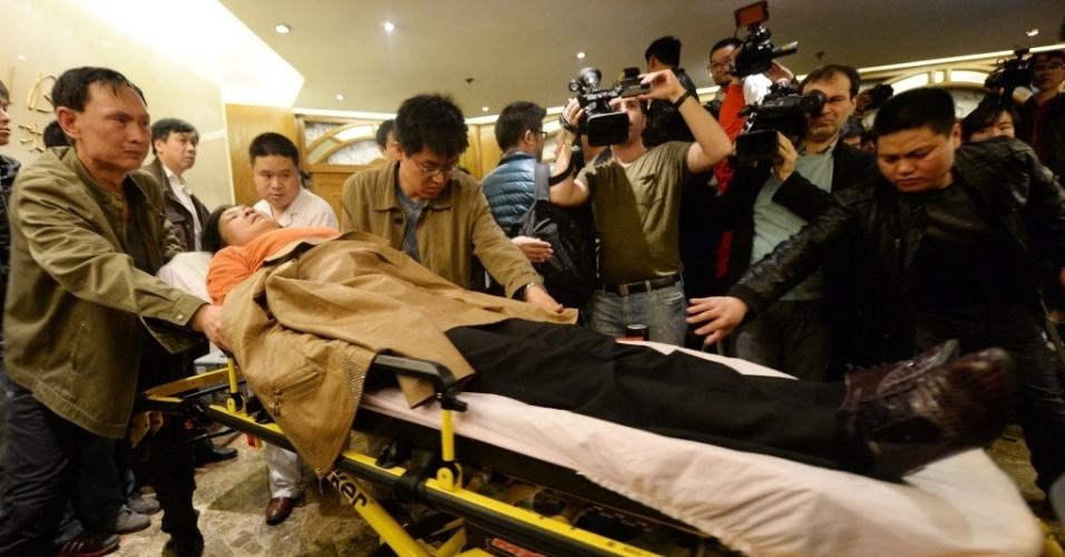 24.mar.2014 - Um familiar de um dos passageiros do vôo MH370 da Malaysia Airlines foi retirado pela equipe médica ao passar mal após receber a notícia de que o avião caiu em uma área remota do oceano Índico e não deixou sobreviventes, no Hotel Lido, em Pequim, na China