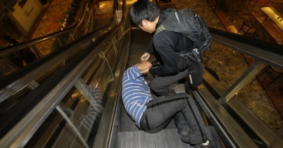 24.mar.2014 - Um parente de um dos passageiro que estava a bordo do voo MH370, da Malaysia Airlines, cai na escada rolante do hotel, Lido, em Pequim, na China, enquanto chora depois de assistir a um programa de televisão com a entrevista coletiva do premiê da Malásia, Najib Razak, que anunciou que a aeronave caiu no sul do oceano Índico e que não há sobreviventes