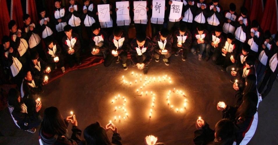 25.mar.2014 - Estudantes seguram velas durante vigília por passageiros do voo MH370 da Malaysia Airlines, em escola na província chinesa de Jiangsu