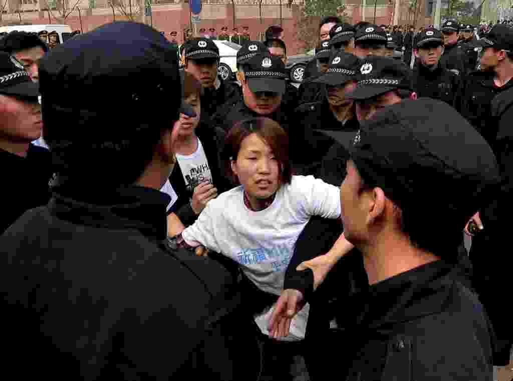 25.mar.2014 - Familiar de passageiro do voo MH370 tenta furar bloqueio policial durante protesto em frente à Embaixada da Malásia em Pequim, na China. Parentes das vítimas exigem mais respostas sobre o acidente aéreo que causou a morte de 239 pessoas - Mark Ralston/AFP