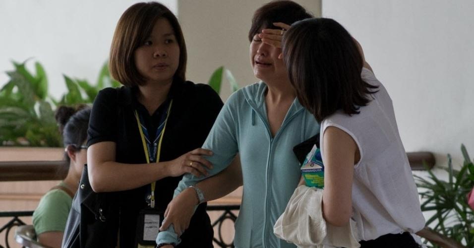 25.mar.2014 - Parente de passageiro chinês do voo MH370 é consolada em hotel em Bangi, próximo a Kulala Lumpur, na Malásia. Autoridades do país foram criticadas pelo anúncio da queda do avião antes que fossem encontrados destroços