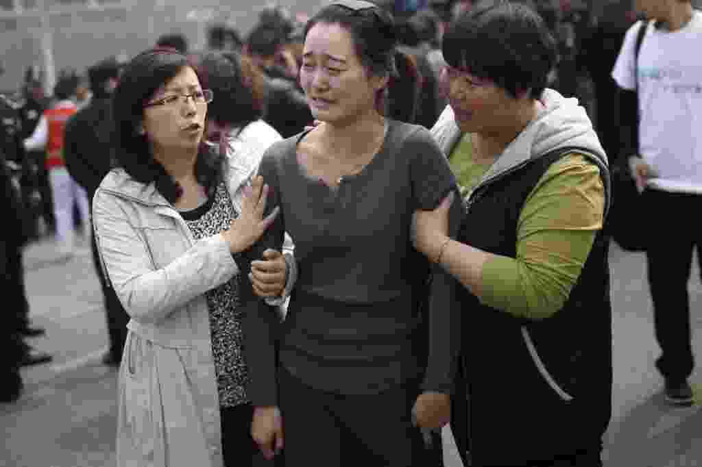 25.mar.2014 - Parente de passageiro do voo MH370 chora em protesto realizado em frente à Embaixada da Malásia em Pequim, na China. Dezenas de familiares dos passageiros foram ao local exigir mais respostas para o acidente que causou a morte de 239 pessoas - AFP