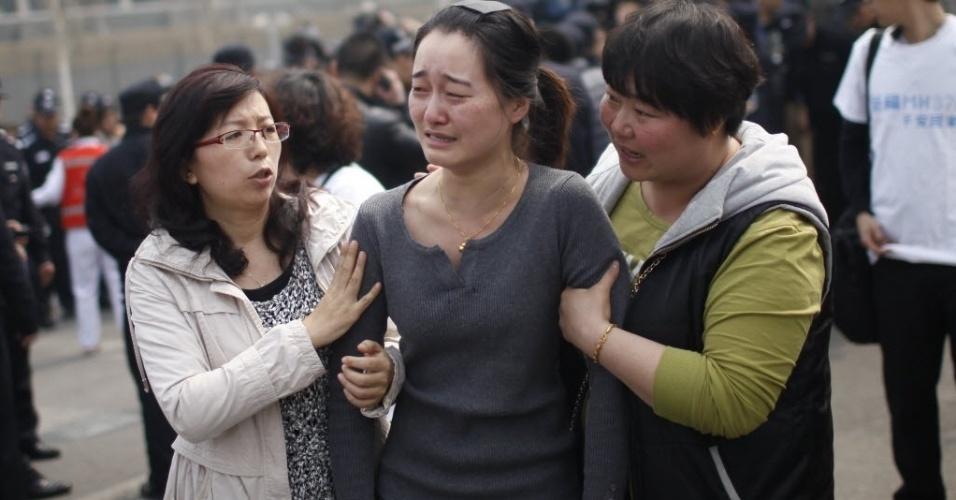 25.mar.2014 - Parente de passageiro do voo MH370 chora em protesto realizado em frente à Embaixada da Malásia em Pequim, na China. Dezenas de familiares dos passageiros foram ao local exigir mais respostas para o acidente que causou a morte de 239 pessoas