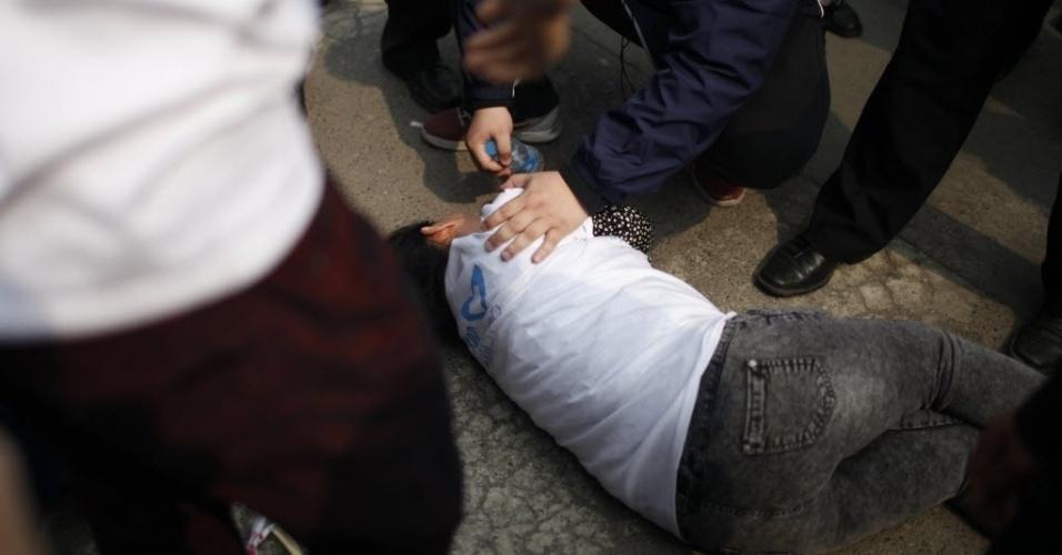 25.mar.2014 - Parente de passageiro do voo MH370 desmaia durante protesto realizado em frente à Embaixada da Malásia em Pequim, na China. Dezenas de familiares dos passageiros foram ao local exigir mais respostas para o acidente que causou a morte de 239 pessoas