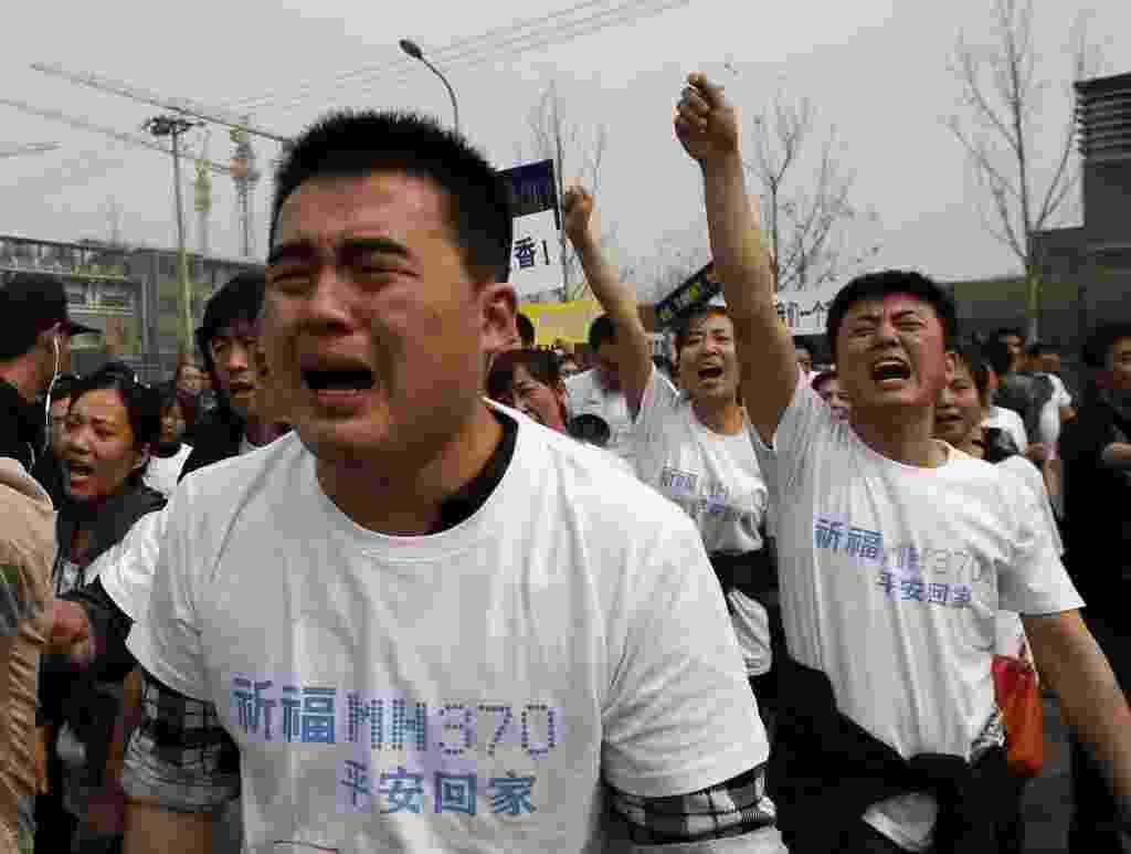 25.mar.2014 - Parentes de passageiros chineses do voo MH370 protestam em frente à Embaixada da Malásia em Pequim. Cerca de 30 pessoas se reuniram no local, exigindo um encontro com o embaixador. Eles acusam a Malásia de ter atrasado as buscas e guardado informações - Kim Kyung-Hoon/Reuters