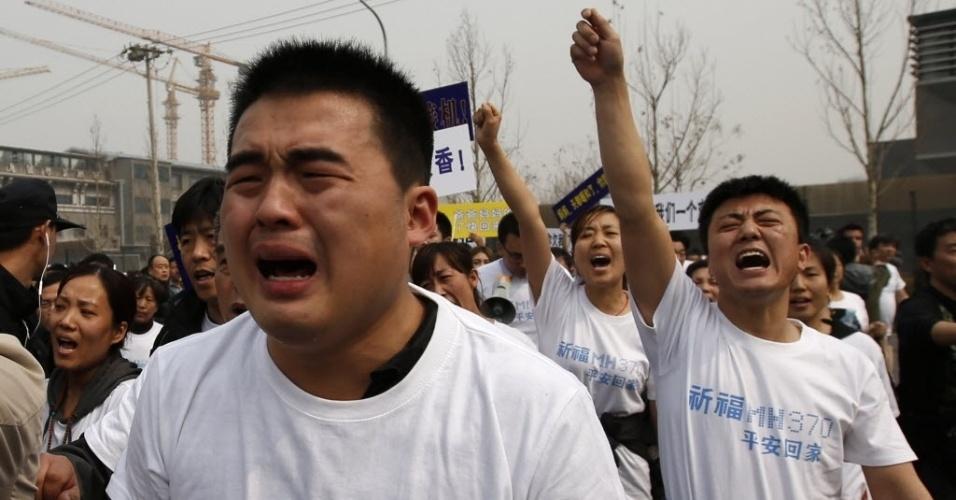 25.mar.2014 - Parentes de passageiros chineses do voo MH370 protestam em frente à Embaixada da Malásia em Pequim. Cerca de 30 pessoas se reuniram no local, exigindo um encontro com o embaixador. Eles acusam a Malásia de ter atrasado as buscas e guardado informações