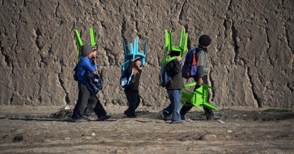 26.mar.2014 - Crianças transportam cadeiras de plástico em direção à escola, em Mazar-i-Sharif. A taxa de alfabetização no Afeganistão é de cerca de 30% e cerca de 42% da população do país está na faixa dos 14 anos. De acordo com a Unicef, mais meninos frequentam as aulas na escola primária do que meninas