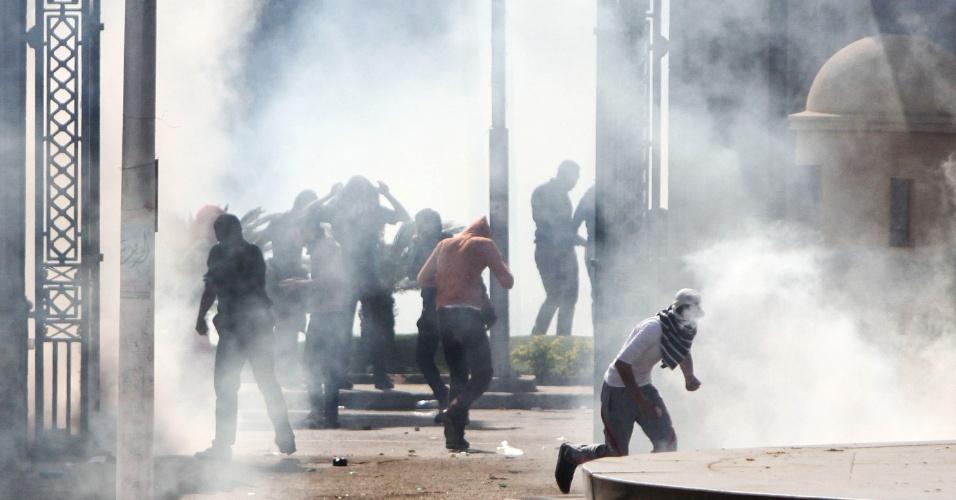 26.mar.2014 - Estudantes egípcios da Irmandade Muçulmana e apoiadores do presidente depoisto Mohammed Mursi correm em meio a fumaça durante confrontos com a polícia após manifestação do lado de fora da Universidade de Cairo