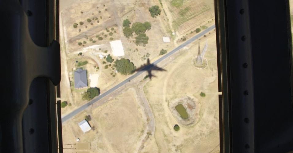 27.mar.2014 - A sombra de um avião chinês é vista em seu retorno de uma missão de busca pelo avião da Malaysia Airlines desaparecido em 8 de março. A China disponibilizou três navios, dois helicópteros e dois aviões para ajudar nas buscas do voo desaparecido no oceano Índico