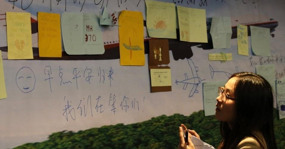 27.mar.2014 - Mulher lê mensagens dedicadas aos passageiros do voo MH370 são mostradas em painel em sala do hotel Lido, em Pequim (China), onde familiares dos passageiros se reuniram com autoridades da Malásia, nesta quinta-feira (27)