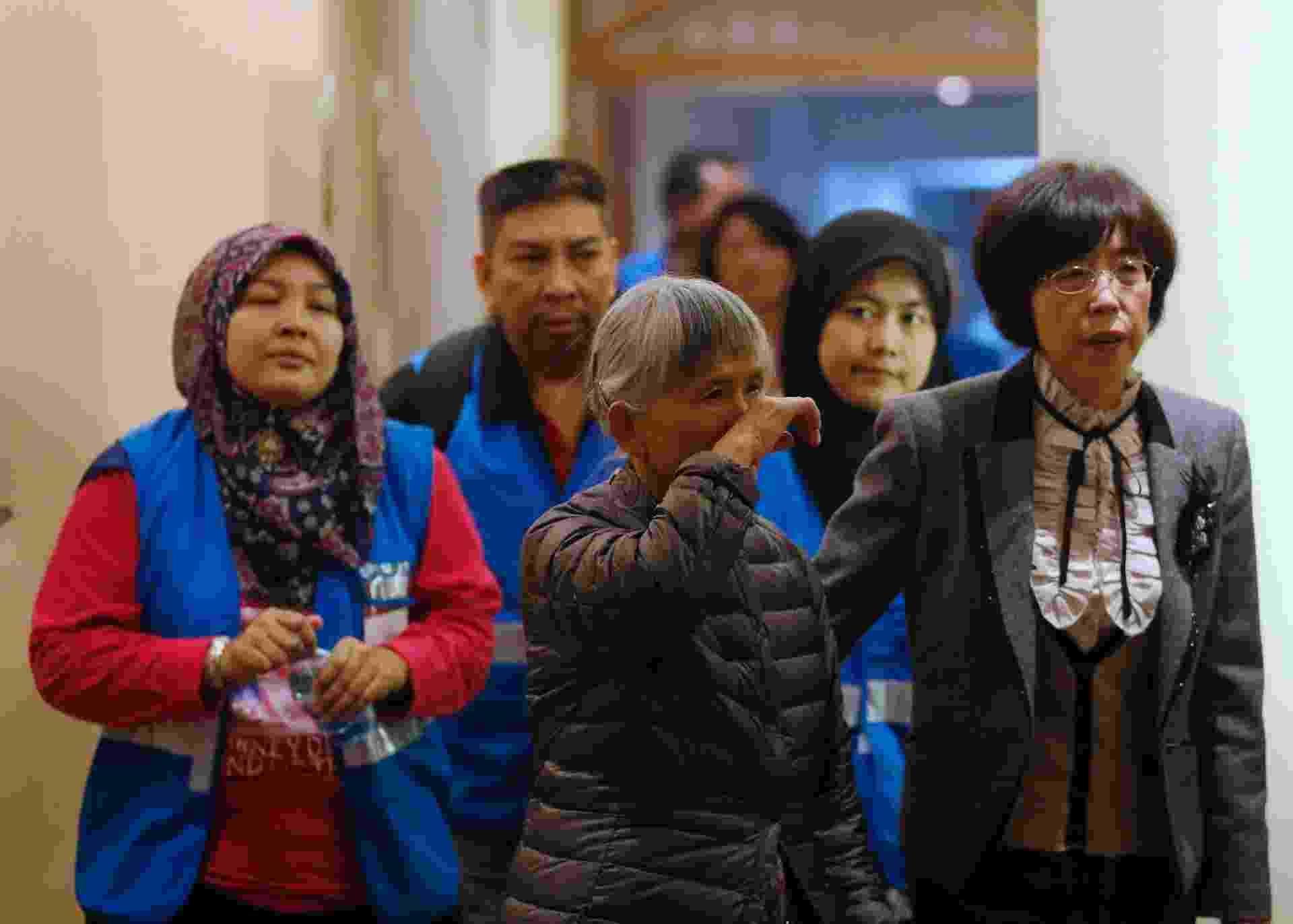 27.mar.2014 - Uma parente de um passageiro do voo MH370 da Malaysia Airlines (ao centro) se dirige a sala de reuniões acompanhada de voluntários da Malásia no Hotel Lido, em Pequim, na China - Kim Kyung-Hoon/Reuters
