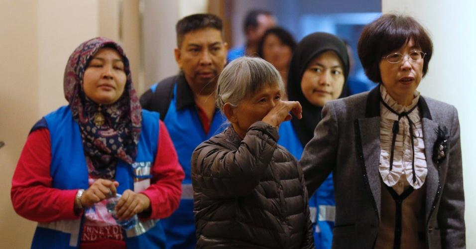 27.mar.2014 - Uma parente de um passageiro do voo MH370 da Malaysia Airlines (ao centro) se dirige a sala de reuniões acompanhada de voluntários da Malásia no Hotel Lido, em Pequim, na China