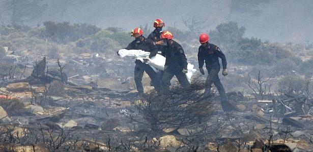 Bombeiros carregam corpo de vítima de acidente com Boeing 737 da Helios Airways, na Grécia, em 2005
