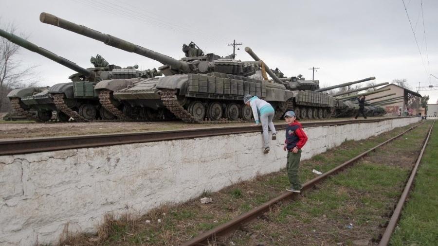 28.mar.2014 - Crianças observam tanques ucranianos na vila Perevalnoe, em uma estação ferroviária na Crimeia - Artur Shvarts/ EPA/ EFE