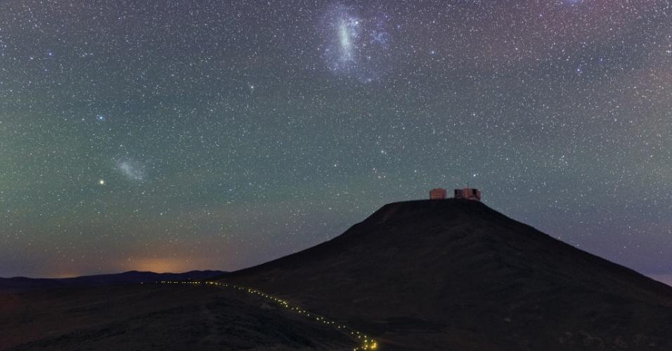 28.Mar.2014 - Expedição de astrônomos está viajando para locais onde estão telescópios da Agência Europeia do Sul para fotografar o espaço da Terra. Aqui, a pequena e grande Nuvem de Magalhães bem acima do monte Paranal, onde está o Very Large Telescope, no Chile