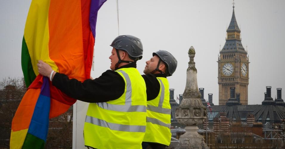 28.mar.2014 - Funcionários do gabinete hasteiam bandeira símbolo do movimento gay no prédio de Whitehall, em Londres, na Inglaterra, nesta sexta-feira (28), para marcar a realização dos primeiros casamentos entre pessoas do mesmo sexo. A lei que autoriza os casamentos entre casais do mesmo sexo entra em vigor neste sábado (29), na Inglaterra e no País de Gales, com dúzias de uniões já programadas para este fim de semana