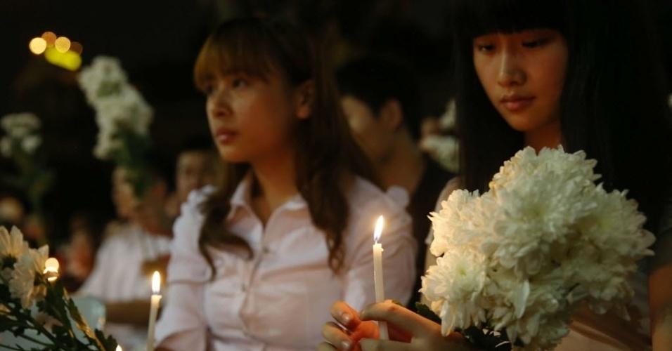 30.mar.2014 - 30.mar.2014 - Pessoas acendem velas em homenagem aos passageiros do voo MH 370, da Malaysia Airlines, em Kuala Lumpur (Malásia), neste domingo (30)