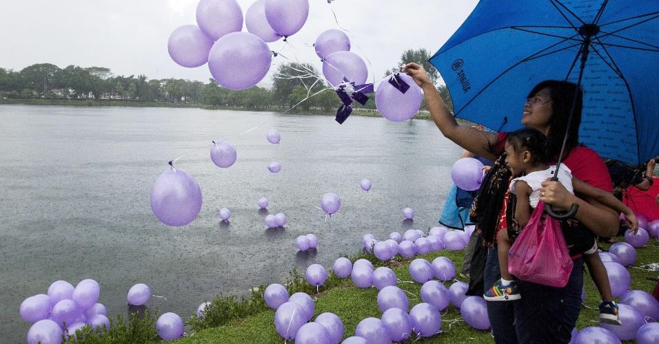 30.mar.2014 - Voluntários soltam balões durante evento em homenagem aos passageiros do voo MH370, da  Malaysian Airline, desaparecido há três semanas. A Malásia continua responsável por coordenar a operação de buscas pelo avião, que ocorre no Oceano Índico