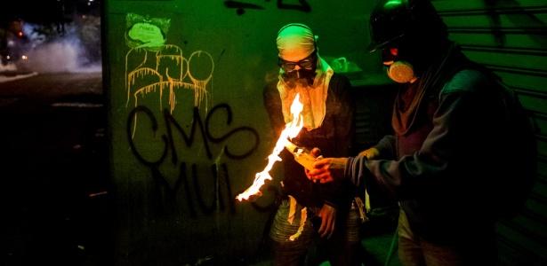 Manifestantes preparam coquetel molotov durante enfrentamento com a polícia venezuelana em Caracas. O presidente venezuelano disse neste domingo (30) que está aberto para suavizar a força contra a oposição se ela aceitar sentar-se à mesa para negociar um fim aos protestos. Duas pessoas morreram neste domingo; em quase dois meses de protesto, houve um total de 39 mortes - Miguel Gutierrez/Efe