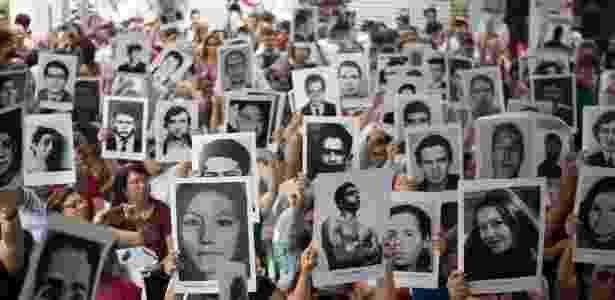 Parentes de desaparecidos políticos, estudantes e integrantes de movimentos sociais seguram cartazes de desaparecidos na época da ditadura militar durante ato no pátio do 36º DP, no Paraíso, zona sul de São Paulo - Danilo Verpa/Folhapress