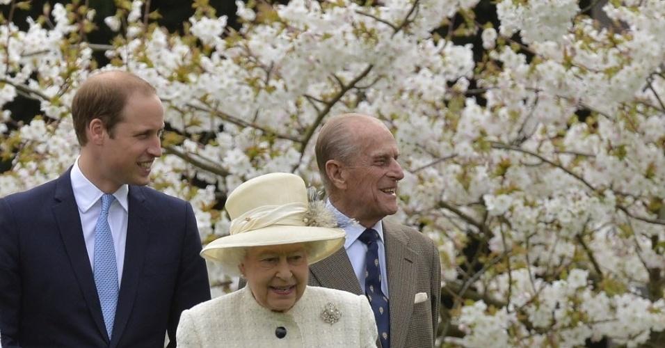 31.mar.2014 - Rainha da Inglaterra, Elizabeth (ao centro), o príncipe Philip (à dir.), e do príncipe William (à esq.), caminham entre flor e as flores da primavera enquanto vão assistir à inauguração da estátua Windsor Greys, em Windsor, sul da Inglaterra