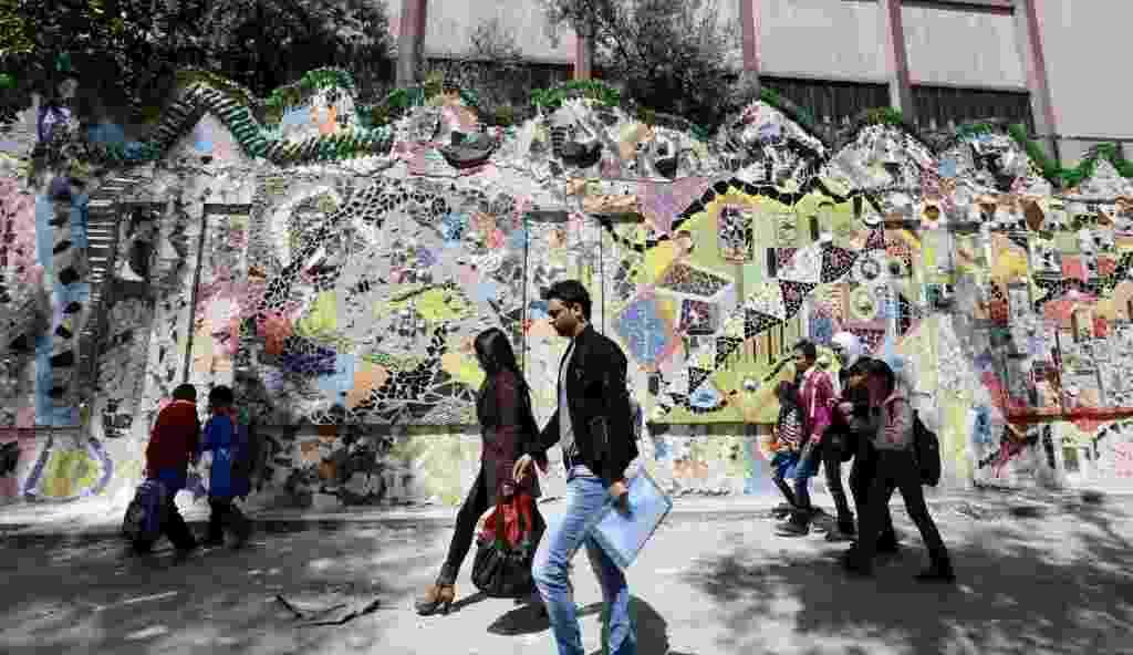 31.mar.2014 - Sírios passam pelo muro decorado que ganhou o título de maior mural feito com material reciclado do mundo pelo Guinness World Records, nesta segunda-feira (31), no bairro de al-Mazzeh, em Damasco, na Síria. O mural tem 720 metros quadrados - Louai Beshara/AFP