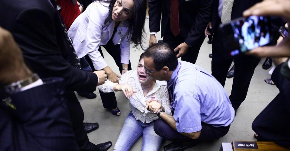 """1º.abr.2014 - A sessão solene realizada nesta terça-feira (1º) na Câmara dos Deputados para lembrar os 50 anos do golpe de 1964 terminou em confusão depois que uma faixa que dizia """"Parabéns aos militares. Graças a vocês o Brasil não é Cuba!"""" foi estendida por militantes na galeria do plenário. Uma mulher que se identificou como Ivone Luzardo, presidente da União Nacional das Esposas de Militares das Forças Armadas do Brasil, caiu no chão durante o conflito"""