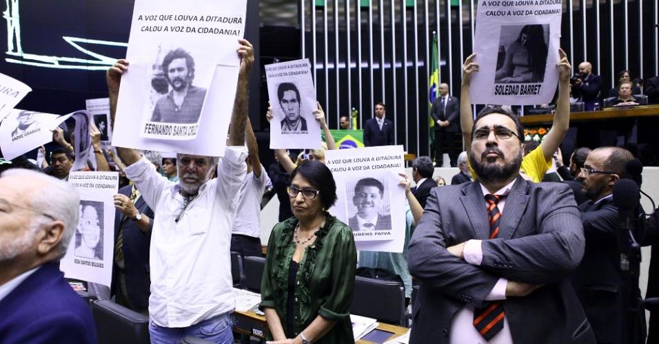 """1º.abr.2014 - A sessão solene realizada nesta terça-feira (1º) na Câmara dos Deputados para lembrar os 50 anos do golpe de 1964 terminou em confusão depois que uma faixa que dizia """"Parabéns aos militares. Graças a vocês o Brasil não é Cuba!"""" foi estendida por militantes na galeria do plenário. Manifestantes mostraram cartazes com  fotos de mortos e desaparecidos políticos"""
