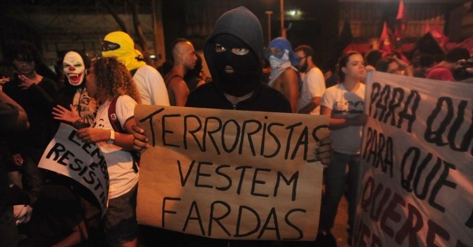 """1º.abr.2014 - Manifestante ergue cartaz onde se lê """"Terroristas vestem fardas"""" durante ato que lembra os 50 anos do golpe que instaurou a ditadura militar no Brasil, na Cinelândia, centro do Rio de Janeiro, nesta terça-feira (1º)"""