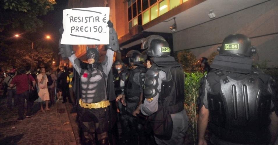 """1º.abr.2014 - Manifestante vestido de Batman ergue cartaz onde se lê """"Resistir é preciso"""" em frente aos policiais durante ato que lembra os 50 anos do golpe que instaurou a ditadura militar no Brasil, na Cinelândia, centro do Rio de Janeiro, nesta terça-feira (1º)"""