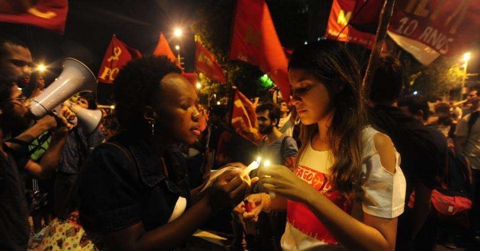 1º.abr.2014 - Manifestantes acendem velas e balançam bandeiras durante ato que lembra os 50 anos do golpe que instaurou a ditadura militar no Brasil, na Cinelândia, centro do Rio de Janeiro, nesta terça-feira (1º)