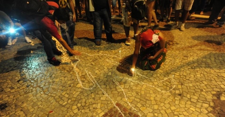 1º.abr.2014 - Manifestantes desenham seus corpos no chão em homenagem aos mortos na ditadura, durante ato que lembra os 50 anos do golpe que instaurou a ditadura militar no Brasil, na Cinelândia, centro do Rio de Janeiro, nesta terça-feira (1º)