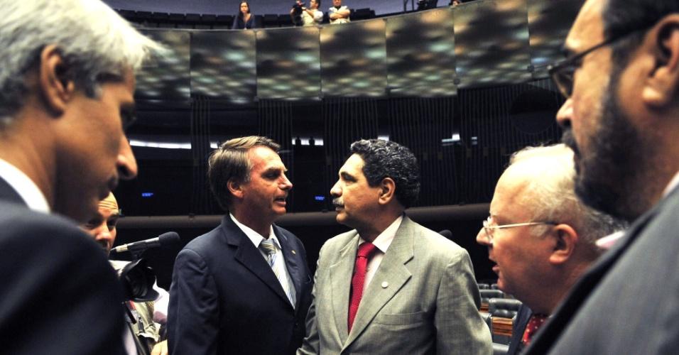 """1º.abr.2014 - O deputado Jair Bolsonaro (PP-RJ) conversa com o deputado João Paulo Lima e Silva (PT- PE) na sessão solene realizada nesta terça-feira (1º) na Câmara dos Deputados para lembrar os 50 anos do golpe de 1964, que terminou em confusão depois que uma faixa que dizia """"Parabéns aos militares. Graças a vocês o Brasil não é Cuba!"""" foi estendida por militantes na galeria do plenário"""