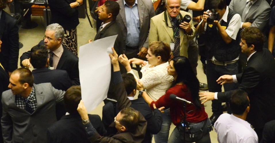 """1º.abr.2014 - Uma mulher que se identificou como Ivone Luzardo, presidente da União Nacional das Esposas de Militares das Forças Armadas do Brasil, precisou de ajuda após ter caído no chão durante o conflito na sessão solene realizada nesta terça-feira (1º) na Câmara dos Deputados para lembrar os 50 anos do golpe de 1964, que terminou em confusão depois que uma faixa que dizia """"Parabéns aos militares. Graças a vocês o Brasil não é Cuba!"""" foi estendida por militantes na galeria do plenário"""