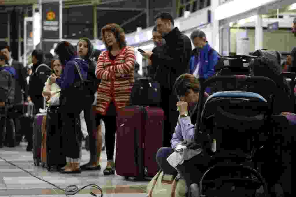 2.mar.2014 - Pessoas aguardam retomada de voos no aeroporto Arturo Merino Benitez, em Santiago, no Chile. Diversos voos foram cancelados após o terremoto de magnitude 8,2 que atingiu o norte do país na noite desta terça-feira (1º) - Xinhua