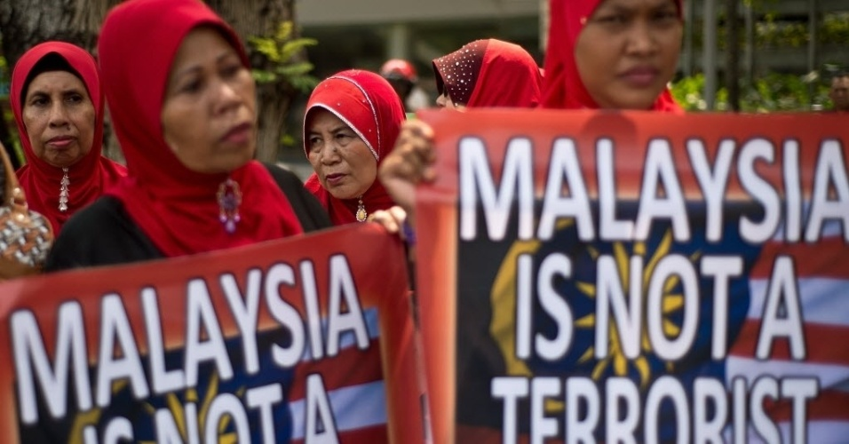 """3.abr.2014 - Ativistas seguram cartazes com os dizeres """"Malásia não é um país terrorista"""", durante protesto contra a cobertura jornalística de canais de televisão americanos sobre o desaparecimento do voo MH370 da Malaysia Airlines, em frente à Embaixada dos Estados Unidos em Kuala Lumpur."""