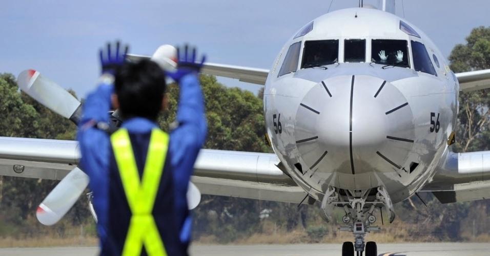 3.abr.2014 - Controlador de voo japonês faz sinal para piloto da Força Aérea do Japão, que se prepara para decolar em base próxima a Perth, na Austrália, para missão de busca do avião da Malaysia Airlines desaparecido em 8 de março