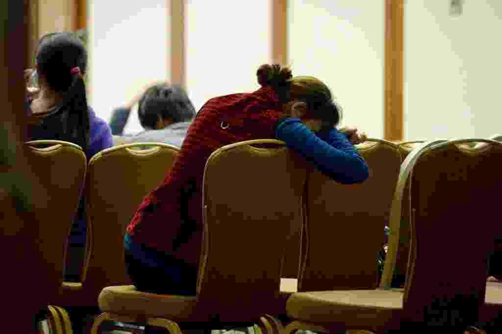 3.abr.2014 - Familiar de passageiro do voo MH370, da Malaysia Airlines, espera por informações em hotel de Pequim, na China. O primeiro-ministro da Malásia afirmou que o país não vai descansar até esclarecer o mistério do voo desaparecido desde 8 de março - Wang  Zhao/AFP