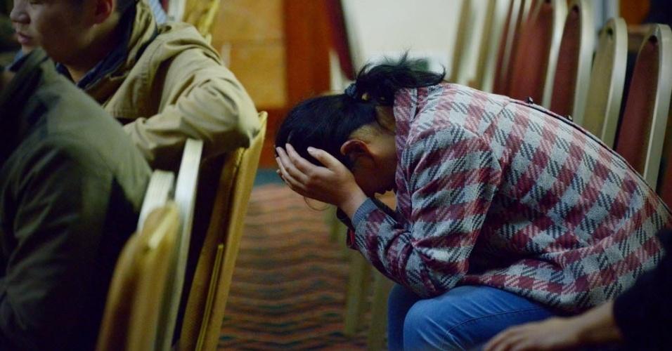 3.abr.2014 - Familiar de passageiro do voo MH370, da Malaysia Airlines, espera por informações em hotel de Pequim, na China. O primeiro-ministro da Malásia afirmou que o país não vai descansar até esclarecer o mistério do voo desaparecido desde 8 de março