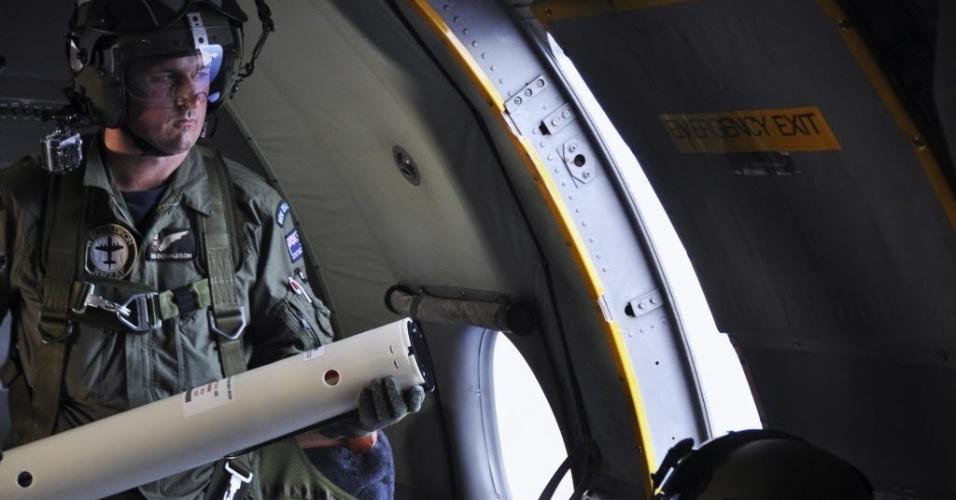 3.abr.2014 - Membro da Força Aérea Real da Nova Zelândia se prepara para lançar sinalização de fumaça para marcar localização de objeto visto no sul do oceano Índico, durante missão de busca do avião desaparecido da Malaysia Airlines
