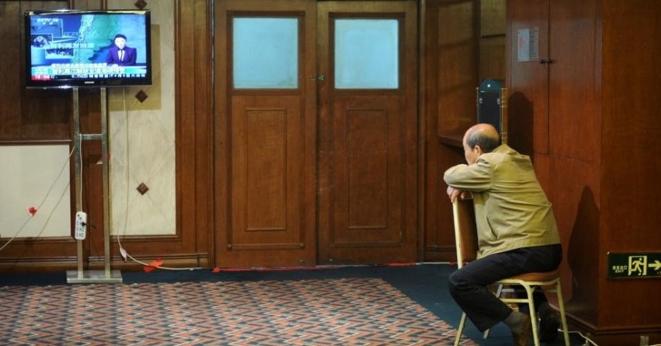 3.abr.2014 - Um parente chinês de um dos passageiros desaparecidos no vôo MH370 da Malaysia Airlines assiste TV enquanto espera por novas informações em um hotel em Pequim, na China